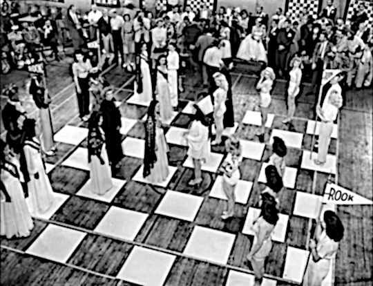 People as chess pieces on a chess board.
